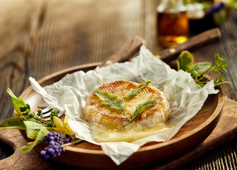 Grilled camembert cheese with addition of herbs on a wooden plate