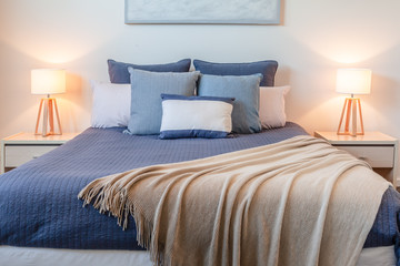 Beautiful arrangement of pillows on bed in a bedroom with bedside lamps and copy space