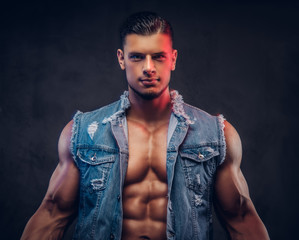 Sexy naked fashionable confident male with a muscular body in a denim vest poses in a studio.