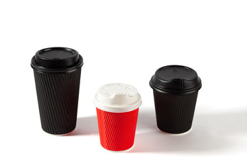 Black and red disposable coffee cups on white background with copy space