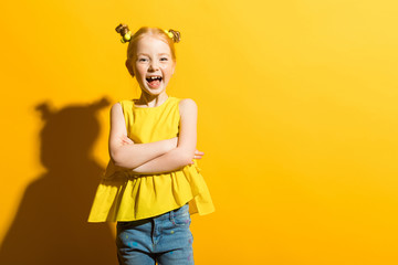Girl with red hair on a yellow background. The beautiful girl laughs and folds her arms across her...
