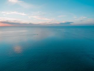 Tiny fishing boat sailing across calm sea at dusk
