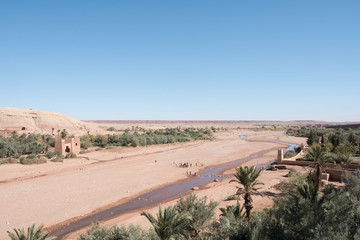 Morocco: photo of old town in sandy mountains in hot summer with blue sky