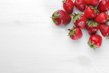 A lot of red strawberries on a white wooden background
