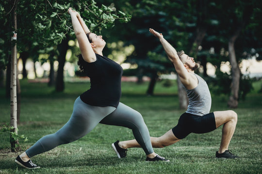 Overweight woman working out with personal trainer