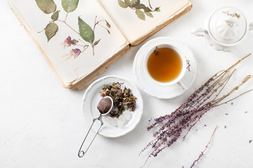 A Cup of tea and a book with a herbarium on a white table