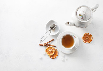 Cup of tea with oranges and cinnamon on a white table. Copy space text