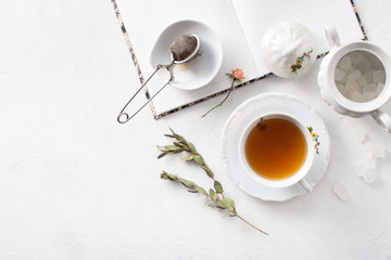 Tea in a Cup with dry flowers on a white table. Copy space text