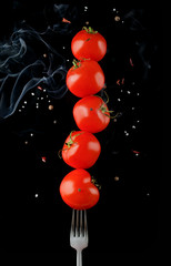 Close up view of levitating cherry tomatoes on fork with salt, spices and some smoke isolated on black