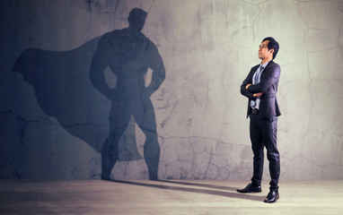 Asian businessman with his shadow of super hero on the wall. Concept of powerful man