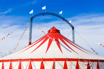 Circus tent under blue sky.  Red and white stripped pattern