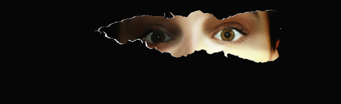 Neugierige junge Frau blickt durch einen Schlitz und schaut erschrocken bzw. erstaunt