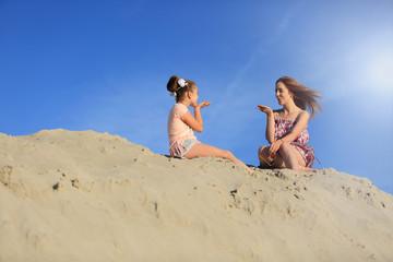 Dwie śliczne dziewczyny przesyłają sobie pocałunki na ogromnej górze piachu.