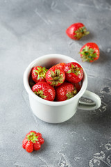 Fresh garden strawberry in enameled mug