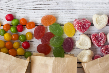 Canvas Prints Candy Sweets in paper bags. Multicolored candy, marmalade in the form of heart on a white wooden background