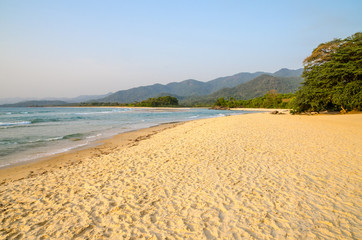 Beautiful Bureh Beach in the afternoon with yellow sand, green trees, sea and mountains, Sierra Leone, Africa