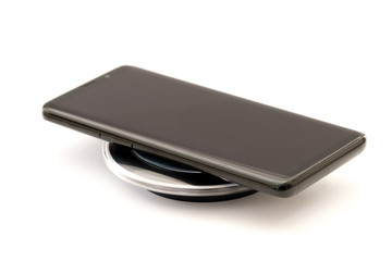 Modern black smartphone charging on wireless charger pad. Isolated on white background with clipping path. Design element.