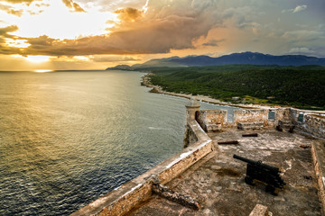 San Pedro de La Roca fort walls with canon, Carribean sea sunset view, Santiago De Cuba, Cuba