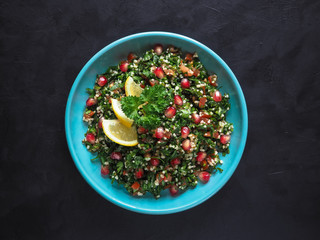 Tabbouleh salad with couscous in a bowl on the black table. Traditional middle eastern or arab dish.
