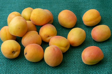 Ripe apricots. Green background. Food for a vegan and a vegetarian. Diet, detox, food concept.