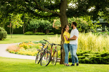 Loving couple in hugging under tree. Young caucasian cyclists hugging on summer nature background. Best travel ever.