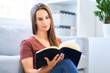 Smiling woman sitting on floor at home and reading a book
