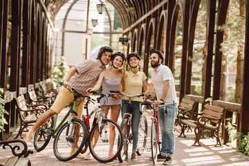 Group of cyclists taking selfie with monopod. Cheerful group of friends enjoying summer vacation by cycling and taking photo.