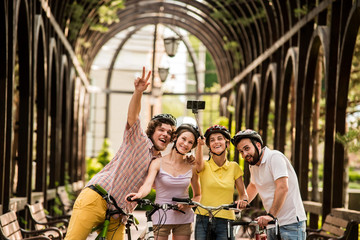 Group of friends taking selfie using monopod. Young funny cyclists posing and taking picture with monopod in park. People having fun.