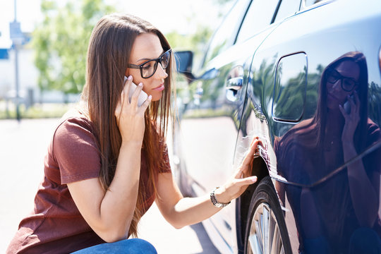 Yougn woman inspecting her scratched car and calling insurance agent
