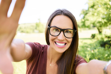 Cheerful young woman taking selfie while in the park during summer