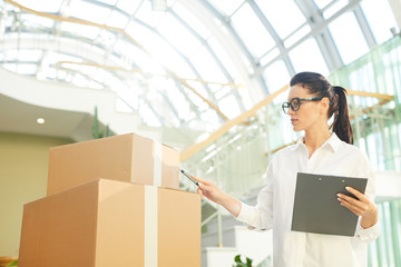 Serious pensive young woman in eyeglasses examining delivered packaged boxes and counting it in glassy room while controlling moving process