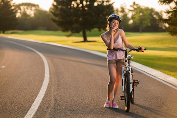 Pretty woman biker posing with bicycle outdoors. Girl with bike on coutry road. Summer relax outdoors.