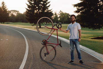 Handsome guy with bicycle resting outdoors. Young cheerful cyclists holding bicycle and looking at camera on country road.