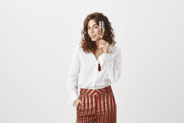 Cheers. Portrait of feminine good-looking confident woman with curly hair, raising glass of champagne, holding hand in pocket and gazing with interest at camera, relaxing with friends on party