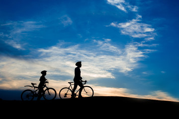 Young couple of cyclists walking at sunset. Young man and woman with bicycles at evening sky background. Amazing rest together outdoors.
