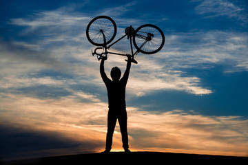 Man lifting bicycle at sunset sky. Silhouette of man lifts bicycle standing on hill on evening sky background. Enjoy your life.