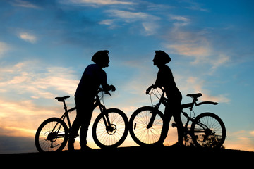 Silhouette of couple on romantic date. Young couple with bikes standing on hill at evening sky. Enjoying of each other.