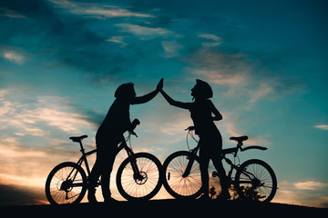 Man and woman giving five with hands outdoors. Couple of cyclists touching hand to hand on evening sky background. Unforgettable rest together.