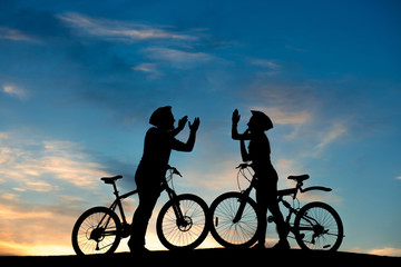 Couple of cyclists clapping hands together. Cheerful couple with bikes having fun on evening sky background. Romantic date on hill at sunset.