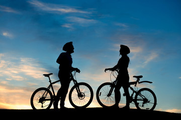 Silhouettes of young people in love at sunset. Loving couple of cyclists enjoying of each other while standing on hill on evening sky background.