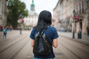 Young woman traveler with a leather backpack walking in an old city Lvov
