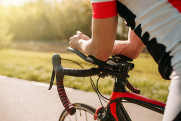 Male bycyclist in sportswear, cycling on bike path