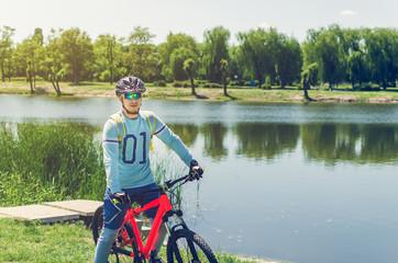 Portrait of a bicyclist wearing a helmet near a river