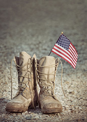 Old military combat boots with the American flag. Rocky gravel background with copy space. Memorial Day or Veterans day concept. Vintage tone.