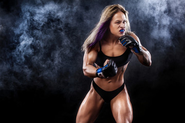 Aggressive sportsman woman boxer fighting on black background with smoke. Copy Space. Boxing sport concept..