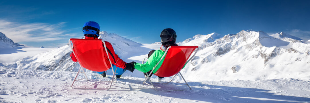 Young couple sitting on deck chairs and enjoying stunning view of Alps, Europe