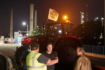 French farmers stand near a parked tractor with a FNSEA union flag on its roof which blocks a road outside the Total refinery in Feyzin