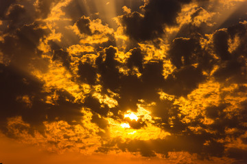 Sunset, the sun shines through the clouds
