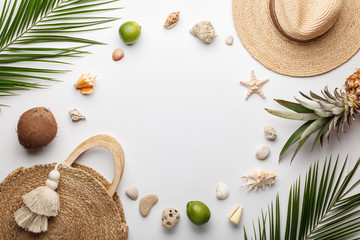 Summer composition. Fruits, hat, tropical palm leaves, seashells on white background. Flat lay, top view, copy space.