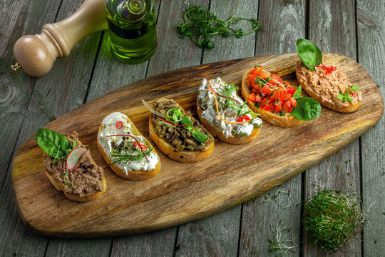 Classic Italian antipasti bruschetta set made of baguette tomato, meat pate, olives, cream cheese and tuna salad on a rustic wooden board. Top view.